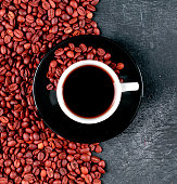 istock top view coffee cup and coffee beans on dark table 1330659203