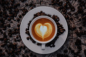 Top view Coffee cup decorated to a heart shape and coffee beans on old wooden floors