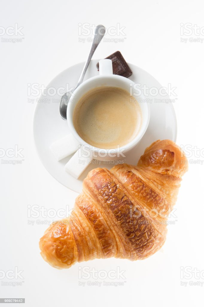 top view coffee in a white cup with a piece of sugar and chocolate and a croissant stock photo