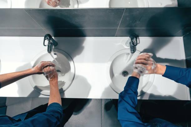 Ansicht von oben . Kollegen waschen sich die Hände in der Bürotoilette – Foto