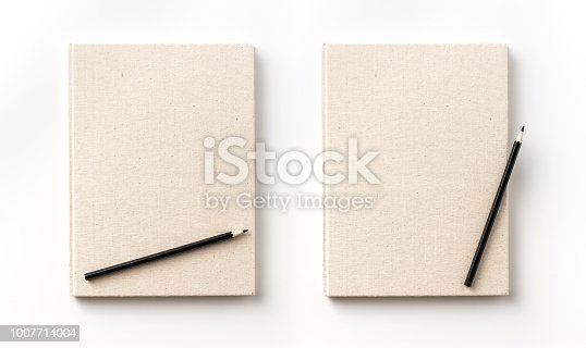 istock Top view collection of  light yellow fabric notebook front, back , pen and white open page isolated on background for mockup 1007714004