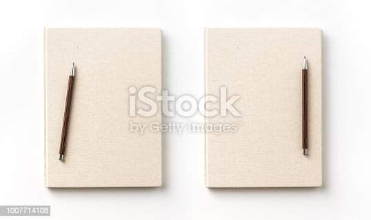 istock Top view collection of  light yellow fabric notebook front, back , pen and white open page isolated on background for mockup 1007714108