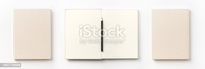 istock Top view collection of  light yellow fabric notebook front, back , pen and white open page isolated on background for mockup 1007716356