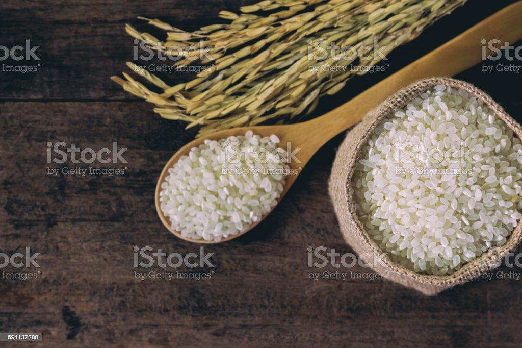 Concepto de la vista superior de arroz japonés. Fondo y la textura del arroz japonés para tu fondo de pantalla y diseño web. Arroz japonés en saco de yute y poner sobre la mesa rústica de madera de la cuchara de madera. - foto de stock