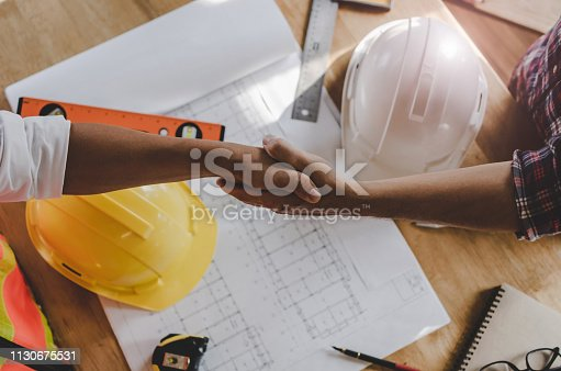 912867216istockphoto top view construction worker team contractor hand shake after finishing up business meeting to greeting start up project contract in construction site building, teamwork, partnership, industry concept 1130675531