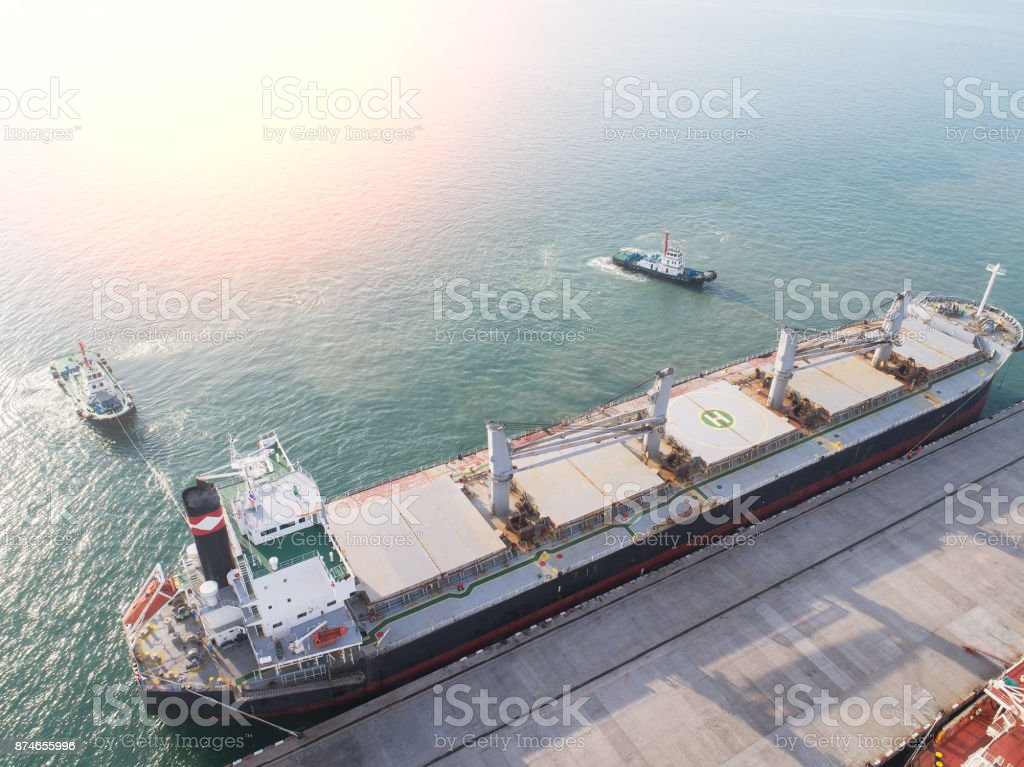 top view container ship commercial vessel alongside in port for loading and discharging containers services in maritime transports in World wide logistics stock photo