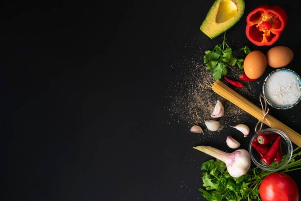 在黑色桌子上烹飪的不同新鮮食材的頂部視圖複製空間 - 材料 個照片及圖片檔