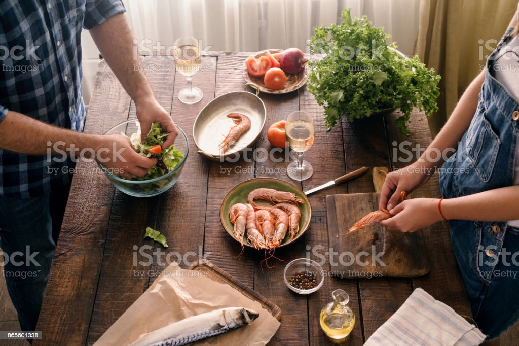 Top view couple cooking together shrimp dinner and salad of vegetables on a wooden table stock photo