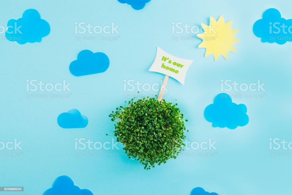 Top view creative collage composition of paper sun, clouds, pointer and fresh green sprouts in round shape as model of our planet. Earth our home concept. Selective focus, space for text. stock photo