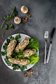 top view cucumbers stuffed with mushroom and nut salad on a white plate, grey cement background with cutlery, concept of menu for restaurant