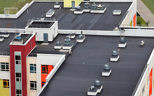 Top view dark flat roof with air conditioners of a modern white red yellow apartment building.