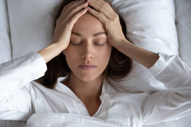 Top view depressed woman suffering from headache, lying in bed stock photo