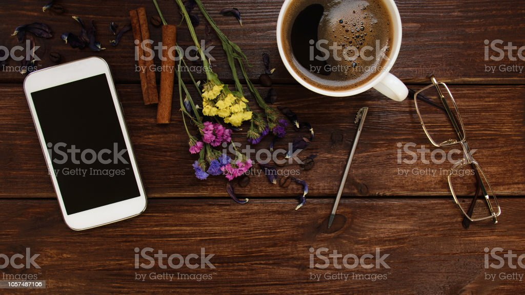 Top view desk dark wood table with smartphone, ebook, cup of coffee,...