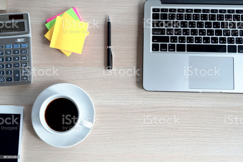 Top view desk of work table in office with laptop computer , notebook , calculator and a cup of coffee for creative business work or marketing plan to success planning of company stock photo