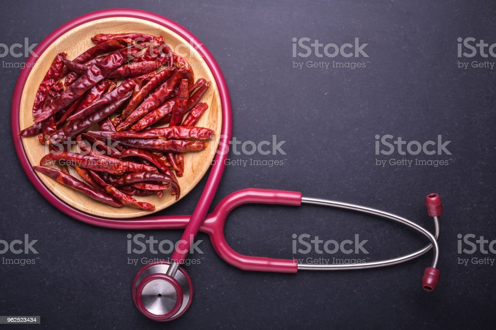 Top view dry red hot chilli and doctor stethoscope on black stone board background - Royalty-free Chili Pepper Stock Photo