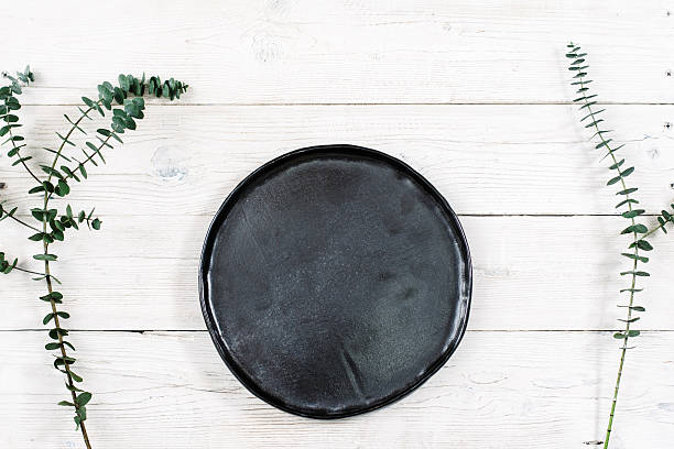 Top view empty black plate on wood stock photo