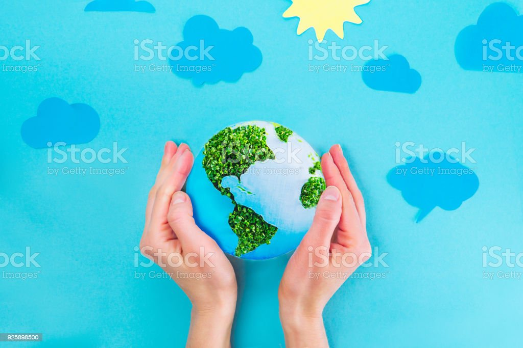 Top view Female Hands holding Earth paper and green sprouts collage model on blue background with paper sun and clouds. Earth in your hands, Saving planet concept. Space for text. stock photo