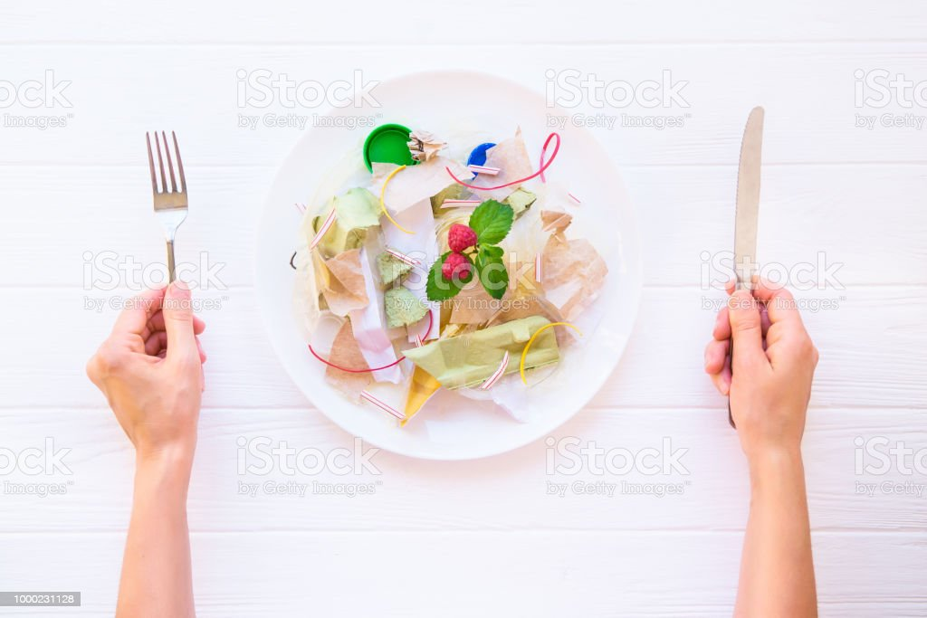 Top view female hands holding knife and fork over the plate with unreal salad from recycle waste, synthetic ingredients. Concept of artificial, food. GMO, E numbers . Chemicals in the food industry. stock photo