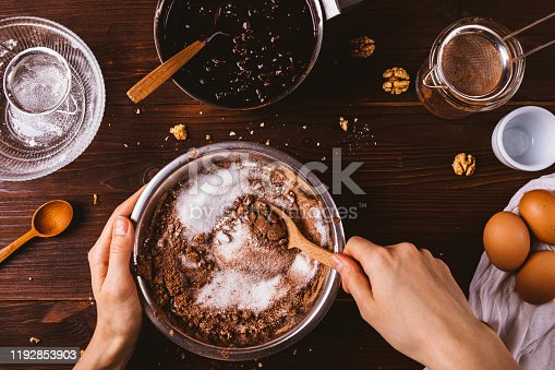 Top view female hands mix cocoa powder, sugar and flour to make dough with melted chocolate and walnuts for delicious homemade brownie cake.