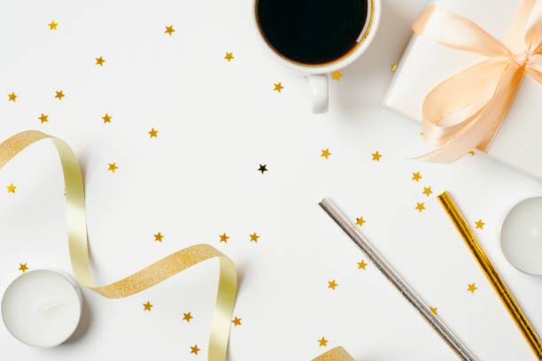 blick auf den femininen schreibtisch mit kaffeetasse und partyzubehör: band, tränengas, geschenkbox, kerzen auf weißem hintergrund. feiertage, hochzeitstag, jubiläum, junggesellenparty, babydusche - tischdeko goldene hochzeit stock-fotos und bilder