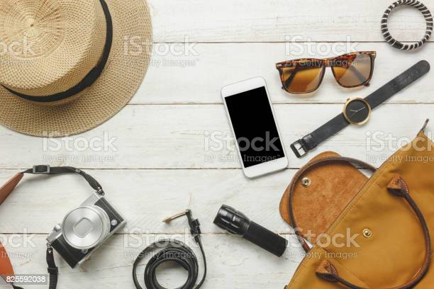Top view / Flat lay accessoire to travel and technology with woman / lady clothing on white wooden table