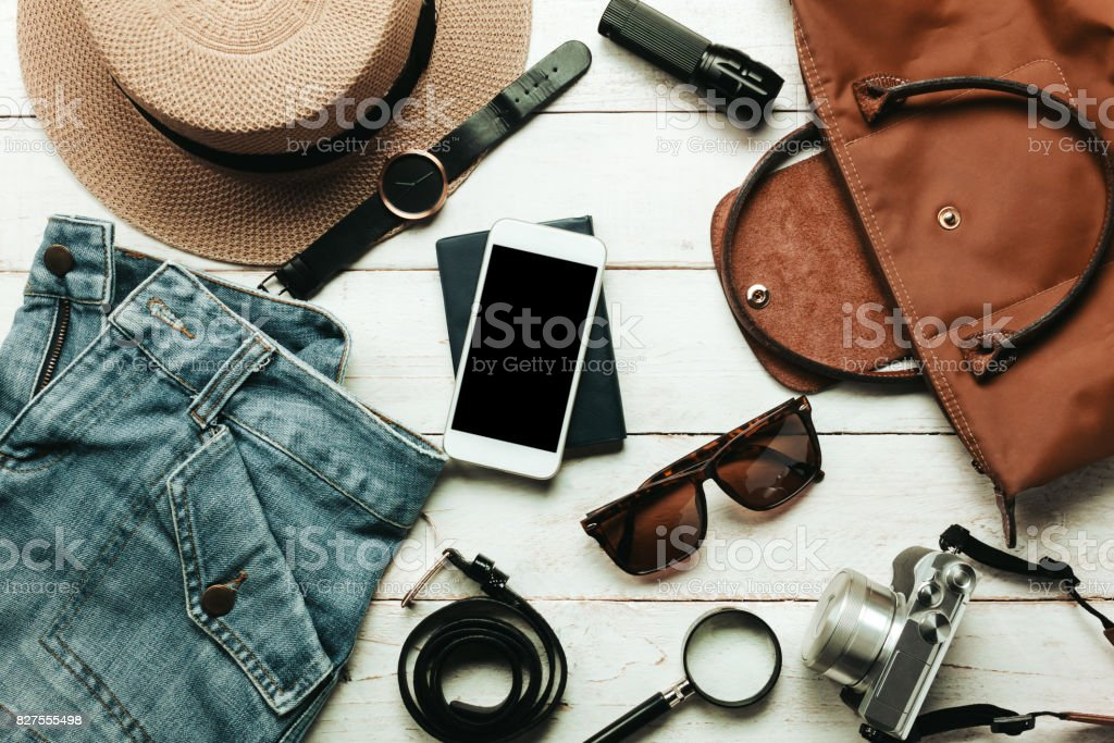 Top view / Flat lay accessory to travel with women / lady or female clothing concept.Essential item white mobile phone, watch,bag,hat,map,camera,necklace,trousers and sunglasses on white wood table. stock photo