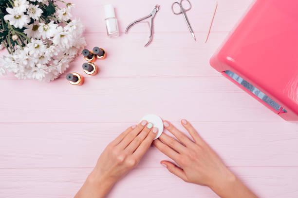 vista superior composição floral feminino mãos remover camada pegajosa - manicure - fotografias e filmes do acervo