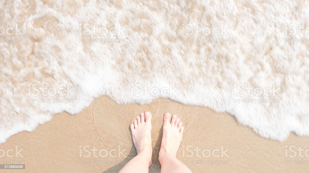 Top view foot on beach with Blur and soften foam stock photo