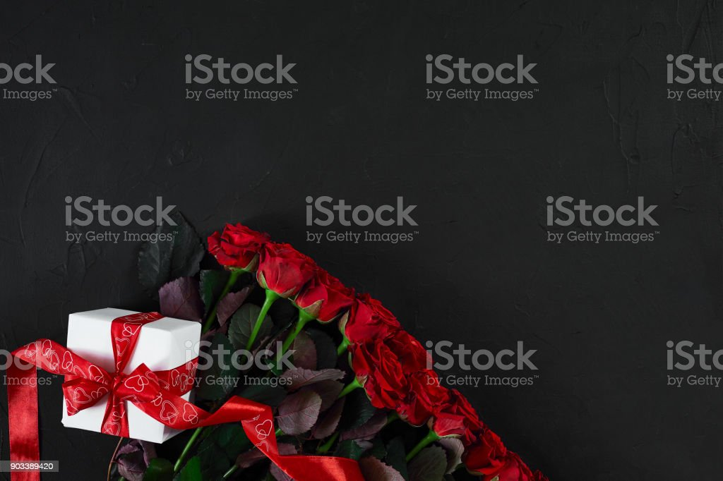 Top view fresh red rose flower and gift box on black deck with empty...