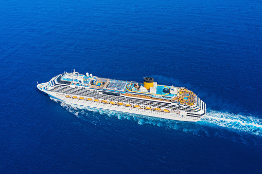 Aerial view of modern large white cruise ship liner with colorful deck against clear blue sea. Top view from drone of floating passenger liner: Valletta, Malta - May 8, 2019
