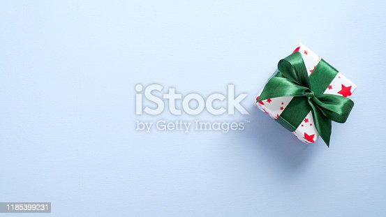 Top view gift box wrapped festive paper with green ribbon bow. Flat lay Christmas holiday present on pastel blue background with copy space. Xmas, New Year, winter holidays concept.