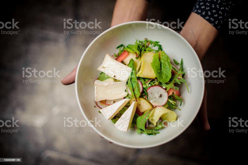 Garota de vista superior, segurando um prato de salada deliciosa - foto de acervo