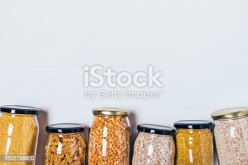 Top view glass jars with variety groats and pasta on white wooden table with free space for text or design.