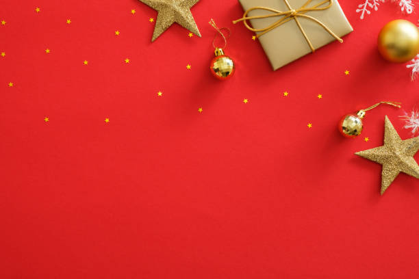 Top view golden Christmas decorations on red background. Flat lay gift box, stars, balls, glittering confetti. New Year greeting card mockup, copy space. Christmas postcard template design.