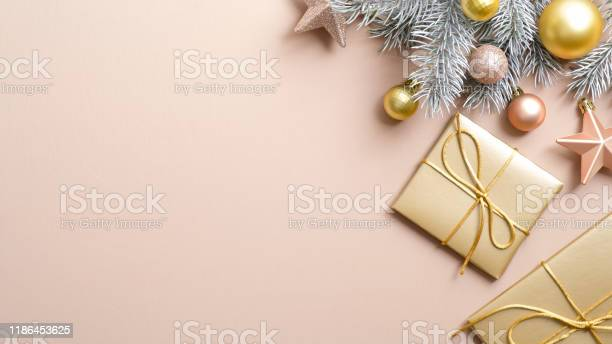 Top view golden christmas gifts and decorations on paste ivory with picture id1186453625?b=1&k=6&m=1186453625&s=612x612&h=wnij16d 56euwm7fy45dxw9gk13jqip6lh5iiwwfxba=