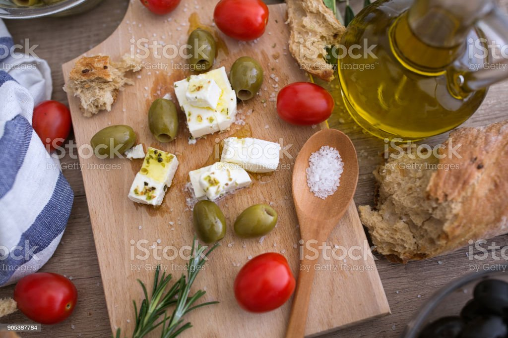 top view Greek cheese feta with virgin olive oil, green olives and fresh vegetables zbiór zdjęć royalty-free