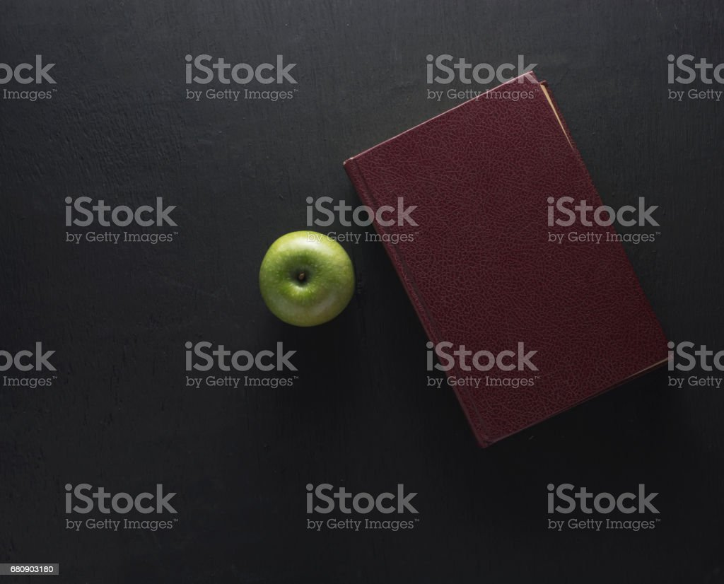 Top view Green apple with old book on black wood background. School concept royalty-free stock photo
