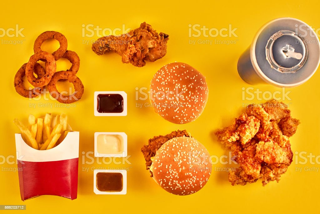 Top view hamburger, french fries and fried chicken on yellow background. Copy space for your text stock photo