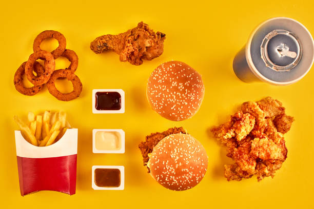 top view hamburger, french fries and fried chicken on yellow background. copy space for your text - fast food restaurant stock pictures, royalty-free photos & images
