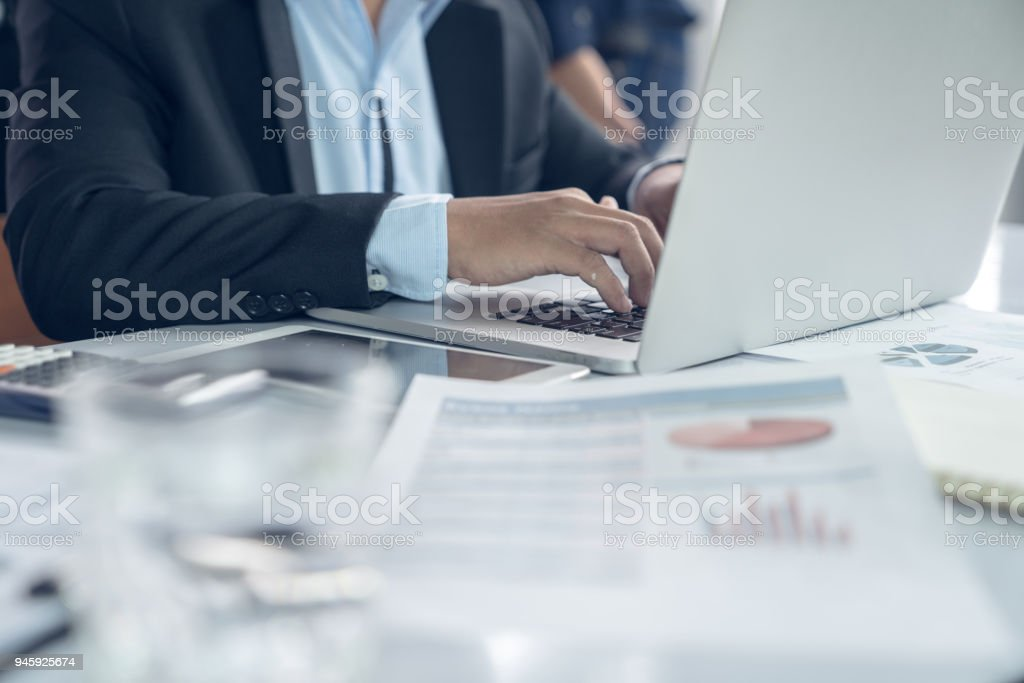 Top view hand of business team during meeting conference are working documents about the marketing plan and sales report profit finance of the company with laptop computer and smartphone tablet on work table stock photo