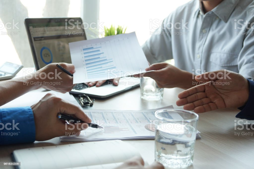 Top view hand of business team during meeting conference are working documents about the marketing plan and sales report finance of the company with laptop computer and smartphone tablet on work table stock photo