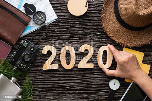 istock top view hand putting 2020 happy new year number on wood table with adventure accessory item,holiday vacation planning 1156667075