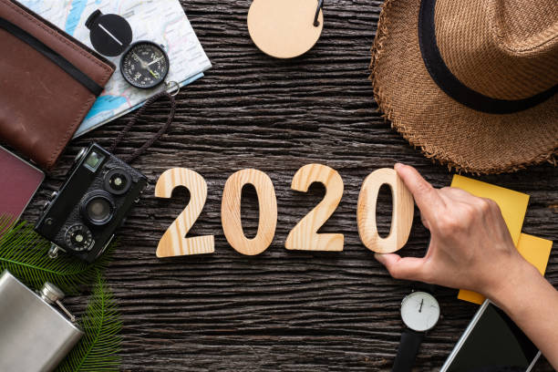 top view hand putting 2020 happy new year number on wood table with adventure accessory item,holiday vacation planning stock photo