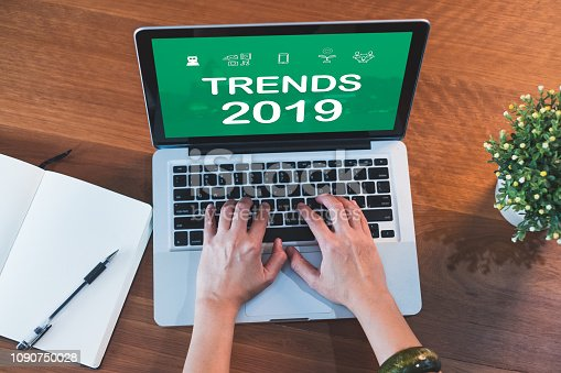 istock top view hand type trends 2019 on laptop keyboard with open notebook and plant on table at home.working with technology. 1090750028