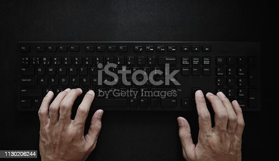 Top view, Hand typing computer keyboard on black background