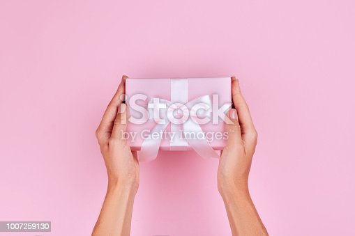 istock top view hand woman holding brown gift box on pink pastel color background 1007259130