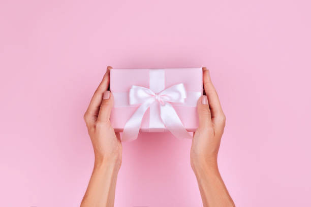 top view hand woman holding brown gift box on pink pastel color background stock photo