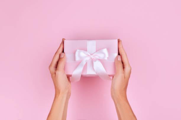 ansicht von oben hand frau mit braunen geschenkbox auf pastell rosa hintergrund - bastelkarton stock-fotos und bilder