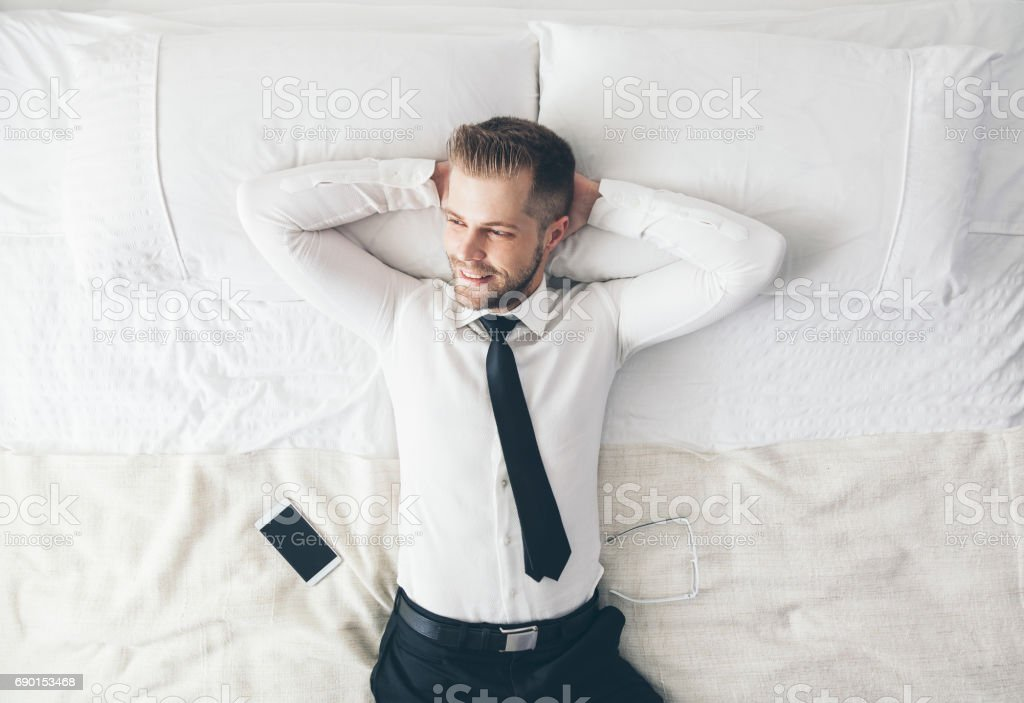 Top view. Handsome businessman relaxing on bed after a tough day at work stock photo