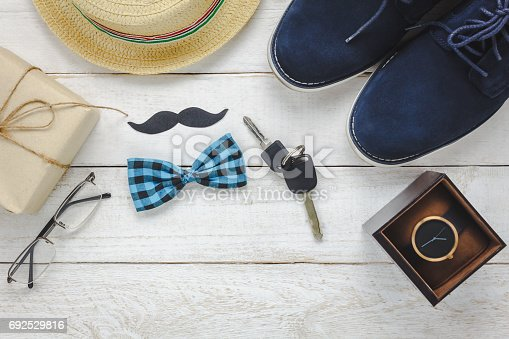 665586146 istock photo Top view Happy Father day on rustic wooden background. accessories with watch,mustache,vintage bow tie,pen,present,key car,shoes and hat. 692529816